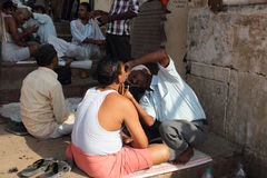 Indian of Varanasi. Hindu devotees are shaving.By the side of the road man is selling a branch sacrifices.Varanasi, also known as Benares, Hindu holy land, a Royalty Free Stock Photo