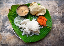 Indian Vegetarian dishes. Homemade Indian vegetarian rice, sambar, grated carrot and poppadoms on the banana leaf at grunge background stock photos