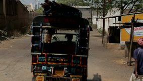 Indian village street. Tuktuk leaves into the distance. A man in a turban. Traditional Indian village street. Tuktuk leaves into the distance. A man in a turban stock footage