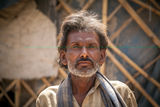 Indian villager man. Close-up of an old face of Indian villager man having wrinkle but little smile on face Stock Image