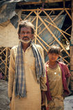 Indian villager man with son. An old Indian villager man having wrinkle but little smile on face with his son Royalty Free Stock Images