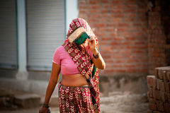 Indian villager woman in veil. With dark complexion going in summer noon Royalty Free Stock Image