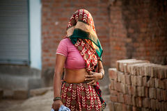 Indian villager woman in veil. With dark complexion going in summer noon Stock Images