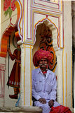 Indian watchman. PUSHKAR, INDIA - NOV 28: Indian watchman with long mustaches standing in its position inside a niche in Pushkar royalty free stock image