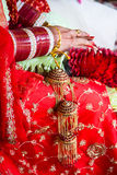 Indian wedding. Bride is sitting in red wedding dress and lots of bracelets in her arms and flowers in her lap Royalty Free Stock Photography