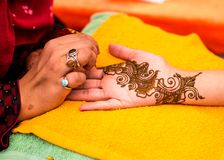 Indian wedding guest having mehndi applied to palm of hand. Traditional henna art. Mehndi artist carefully painting an intricate design using henna, to the open stock image