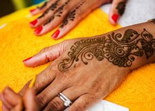 Indian wedding guest having mehndi applied. Traditional henna art. Mehndi artist carefully painting an intricate design using henna, on the forearm of young royalty free stock image