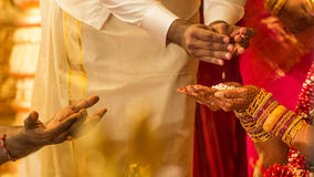Indian wedding rital. Flowers are passed to the bride's hands from her farther during a south Indian Hindu wedding the Hindu priest's hands can be seen to the Stock Image