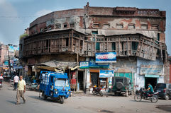 Indian widespread city picture with old building. Amritsar, India - August 26, 2011: Old damaged building with shops and car services on first floor, located Royalty Free Stock Photos