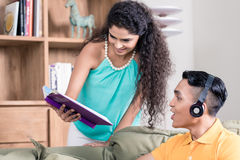 Indian wife showing her husband book she is reading Royalty Free Stock Image
