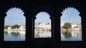 Through Indian window. Beautiful morning lakeside view though indian style window. Wonderfull white palace mirroring on the lake. Udaipur, India Royalty Free Stock Images