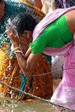 Indian woman. Washing her face with holy water Royalty Free Stock Images