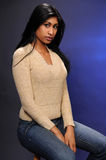 Indian woman. Beautiful young Indian woman in a beige knit blouse and blue jeans stock image