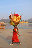Indian woman with basket on her head walking by Man Sagar Lake Stock Images