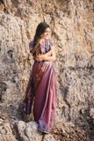 Indian woman in beautiful saree. Fashion shoot of indian woman in traditional clothes. Woman in beautiful saree standing on the rock near the beach Royalty Free Stock Photography