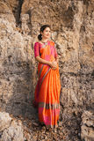 Indian woman in beautiful saree. Fashion shoot of indian woman in traditional clothes. Woman in beautiful saree standing on the rock near the beach Royalty Free Stock Images