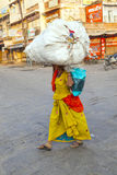 Indian woman carries heavy load on Stock Photo