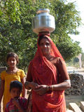 Indian woman carries metal water pot on her head Stock Image