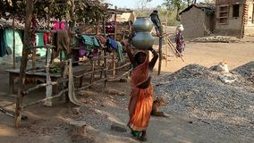 Indian woman carry baskets of water on her head stock video footage