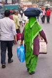 Indian woman carrying bundle on her head, New Delhi, India Royalty Free Stock Photography