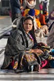 Indian woman with child sitting near the lake at Golden Temple. Amritsar. India Stock Photography