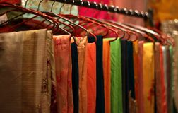Indian woman clothes Sarees or Saris on hangers. Closeup of Indian woman clothes Sarees or Saris on hangers in display of a retail shop or store royalty free stock image