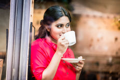 Indian woman with coffee mug. And flirty expression royalty free stock images