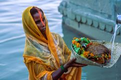 Indian Hindu woman devotee offering prayers to the Sun God during Chhath Puja in Varanasi. Indian woman devotee wearing a yellow sari standing in the waters of royalty free stock photo