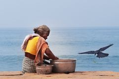 Indian woman with dish fish on Samudra beach in Kovalam. KOVALAM, INDIA - DEC 28, 2014: Unidentified Indian woman with dish fish on Samudra beach in Kovalam royalty free stock images