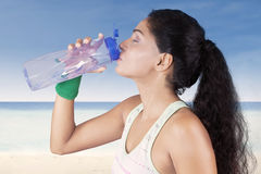 Indian woman drinking water at beach Stock Photography