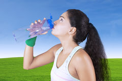 Indian woman drinks water in meadow Stock Photo