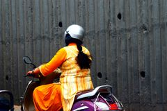 Woman is driving a bike stock. An Indian woman is driving her bike on the city streets in India and wearing Indian traditional cloths stock photograph royalty free stock photo