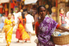 Indian woman with flowers. Indian woman carrying a basket of flowers for sale in Madurai Royalty Free Stock Photo