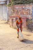 Indian Woman of the fourth Caste cleaning the streets of Jaipur, India. JAIPUR, INDIA - 20 NOVEMBER: woman of fourt class in brightly colored clothing cleans the Royalty Free Stock Photo