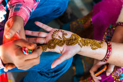 An Indian woman gets henna tattoos on the hands. India royalty free stock images