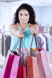Indian woman gives shopping bags at store Stock Photo