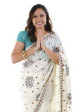 Indian woman greeting. Mid Adult Indian woman in a greeting pose, isolated white background Stock Photo