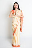 Indian woman in greeting pose. Full length mixed race Indian Chinese female with sari dress in greeting gesture, standing on plain background Royalty Free Stock Image