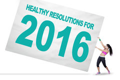 Indian woman and healthy resolutions for 2016. Image of Indian woman wearing sportswear pull a big board with a text of healthy resolutions for 2016 Royalty Free Stock Photography