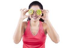 Indian woman holding kiwi fruit on her eyes Stock Image