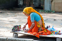 Indian woman iin colorful sari sells souvenirs Royalty Free Stock Photos