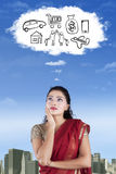 Indian woman imagines her wish. Indian woman wearing saree clothes and imagines her wish on the cloud speech bubble royalty free stock photo