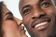 Indian woman kissing black man on cheek. Stock Image