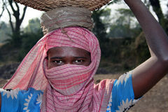 Indian woman labour. An Indian tribal woman labour of stone crusher wrapped her face with a piece of cloth to prevent heat and dust is holding a bucket full of Stock Image