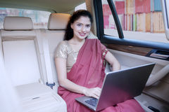 Indian woman with laptop smiling in car. Young Indian businesswoman smiling at the camera while working with a laptop computer in a car. Shot with container on Stock Images