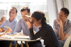 Indian woman laughing eating pizza with diverse coworkers in off. Indian women laughing at funny joke eating pizza with diverse coworkers in office, friendly stock photos