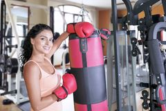 Indian woman leaning on boxing bag stock images