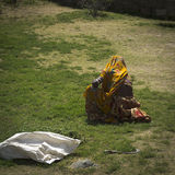 Indian woman from a low caste. An Indian woman, from a low caste, is wearing a yellow sari. She  is squatting to cut the grass Royalty Free Stock Photography