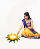 Indian woman making rangoli using flowers. Indian woman or young girl making floral or flower rangoli for diwali or onam, isolated over white background Royalty Free Stock Photo
