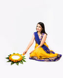 Indian woman making rangoli using flowers. Indian woman or young girl making floral or flower rangoli for diwali or onam, isolated over white background Stock Photo